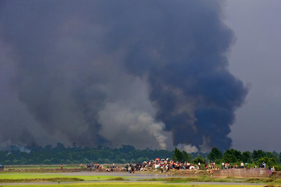 Rohingya refugees seen from afar crossing the border from Myanmar with big smoke and fire in the background covering most of the image